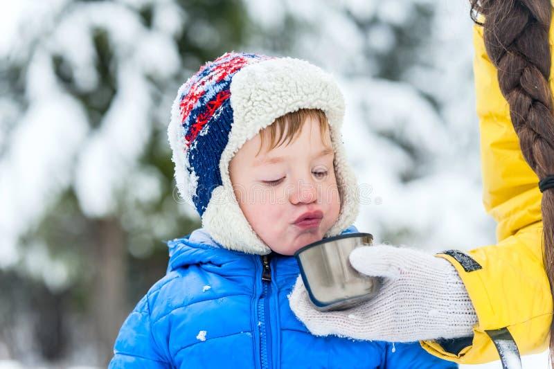 Niño al aire libre del retrato que sopla en té caliente de un termo en wint fotos de archivo
