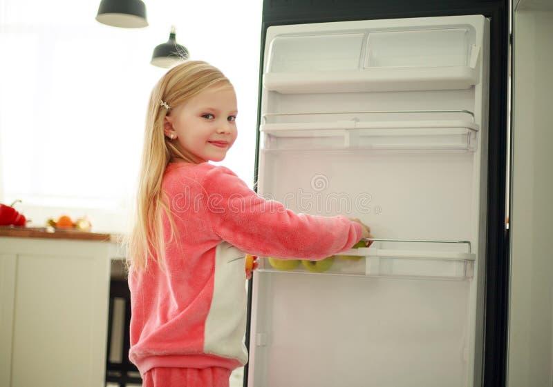Niño alegre de la muchacha cerca del refrigerador que sostiene una manzana en manos, comida sana como forma de vida fotografía de archivo libre de regalías