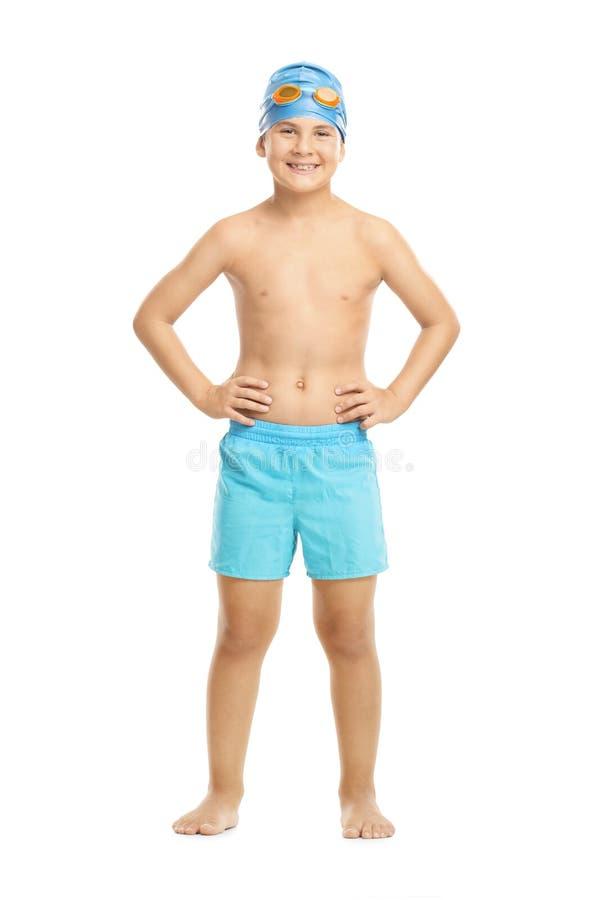 Niño alegre en traje de baño con las gafas del casquillo y de la natación de la nadada imagen de archivo