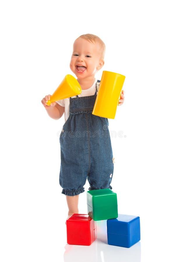 Niño alegre feliz que juega con los cubos de los bloques aislados en blanco imágenes de archivo libres de regalías