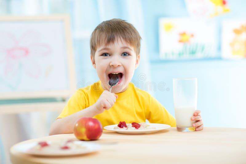 Niño alegre que come la comida sana en casa o imagenes de archivo