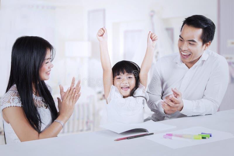 Niño alegre que consigue aplauso de sus padres imagen de archivo