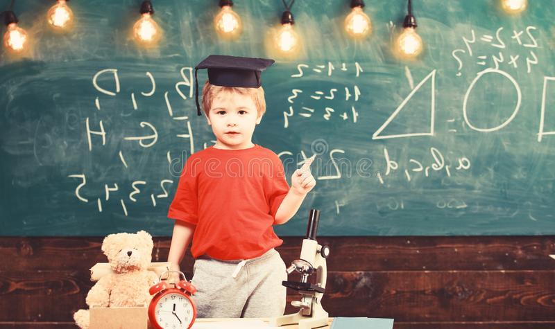 Niño, alumno en cara tranquila cerca del microscopio Primer interesado anterior en estudiar, aprendiendo, educación Concepto del  foto de archivo libre de regalías