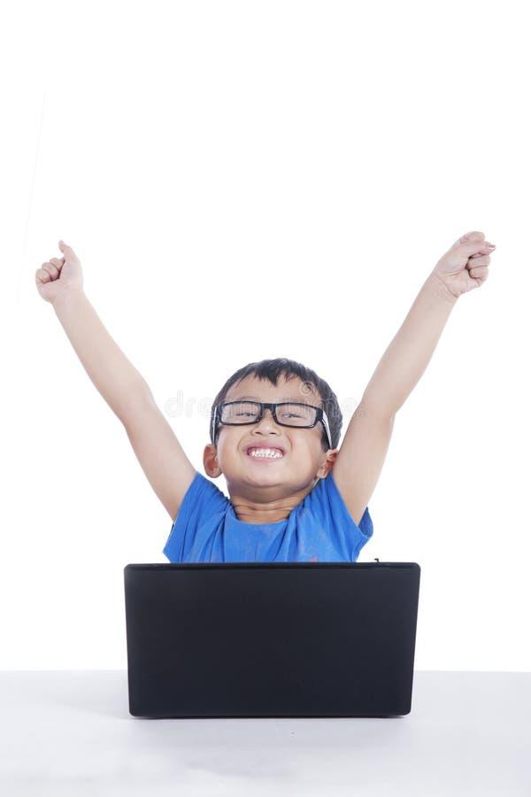 Niño asiático con la computadora portátil usando la computadora portátil fotos de archivo