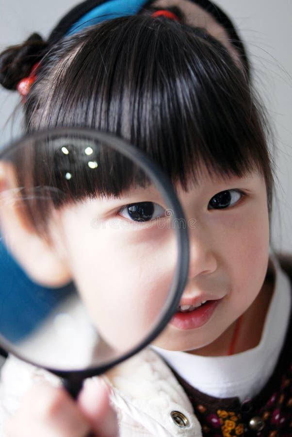 Niño asiático con la lupa imagenes de archivo