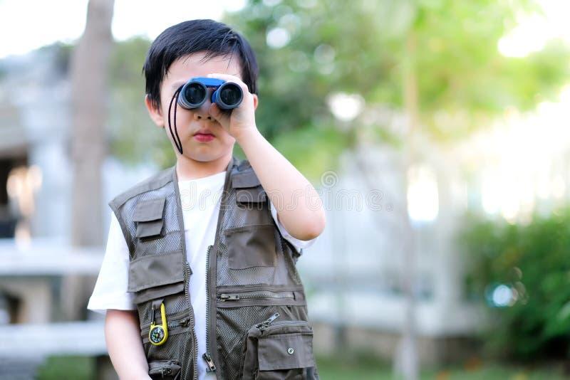 Niño asiático curioso mirando a través de los prismáticos en el jardín Actividad al aire libre Me siento divertido fotografía de archivo