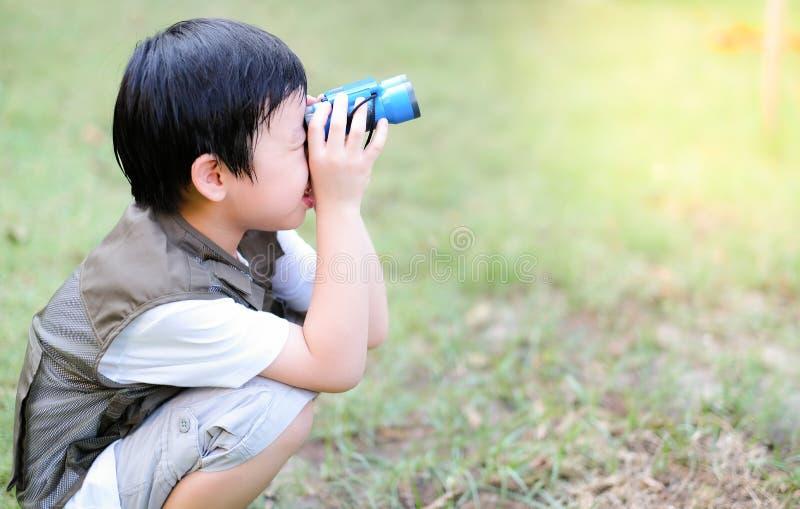 Niño asiático curioso mirando a través de los prismáticos en el jardín Actividad al aire libre Sentirse divertido y feliz imagen de archivo