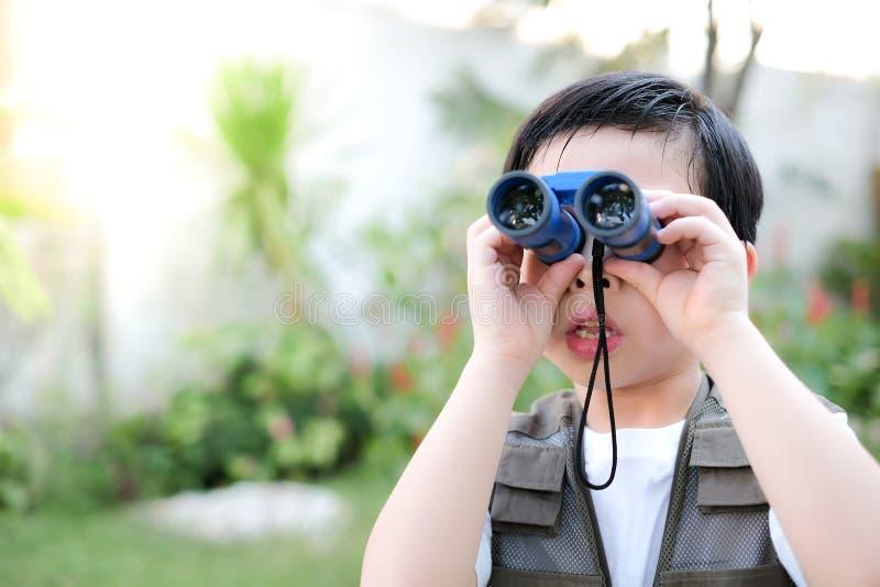 Niño asiático curioso mirando a través de un prismáticos azules en el jardín imagen de archivo