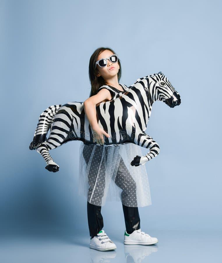 Niño asiático del bebé en la ropa y las gafas de sol de la alta moda que van al partido del acontecimiento con el globo metálico  fotos de archivo