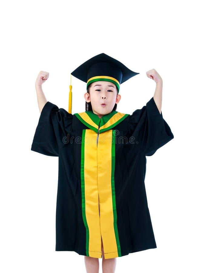 Niño asiático en vestido de la graduación con sus manos para arriba Aislado en wh foto de archivo libre de regalías