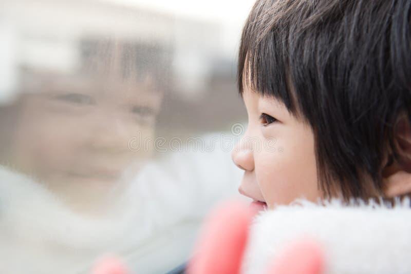 Niño asiático feliz que mira hacia fuera la ventana del tren afuera imágenes de archivo libres de regalías