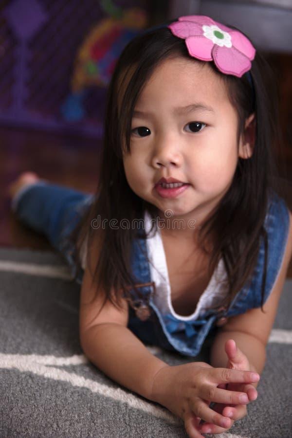 Niño asiático femenino que pone en el piso que sonríe en la cámara imagen de archivo libre de regalías