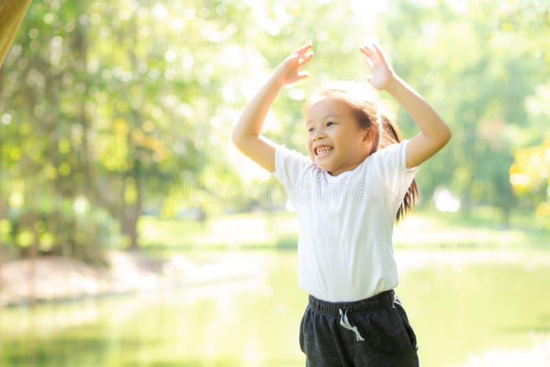 Niño asiático joven hermoso que sonríe y que juega alegre en el parque, el salto del niño de Asia y la diversión confiados en el  imagen de archivo libre de regalías