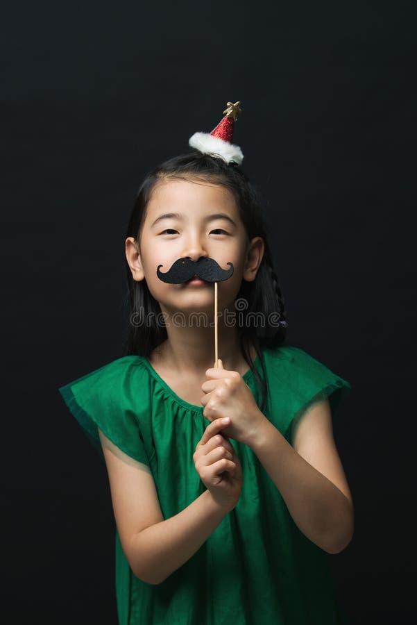 Niño asiático lindo de la mujer con la decoración principal falsa del bigote y de la Navidad en fondo negro imagen de archivo