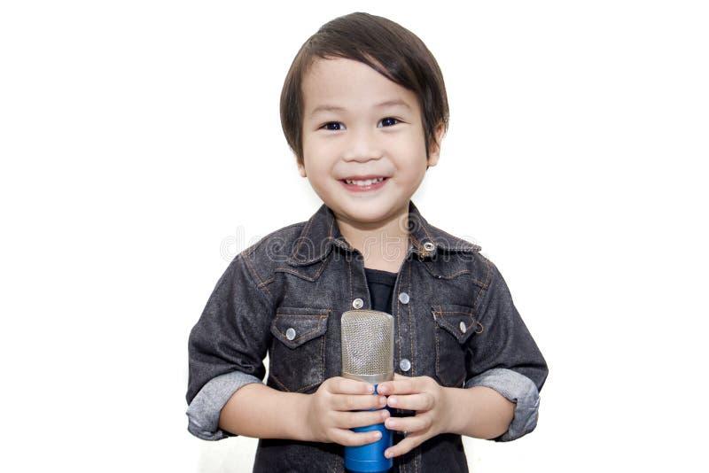 Niño asiático lindo que canta en fondo blanco aislado fotos de archivo libres de regalías