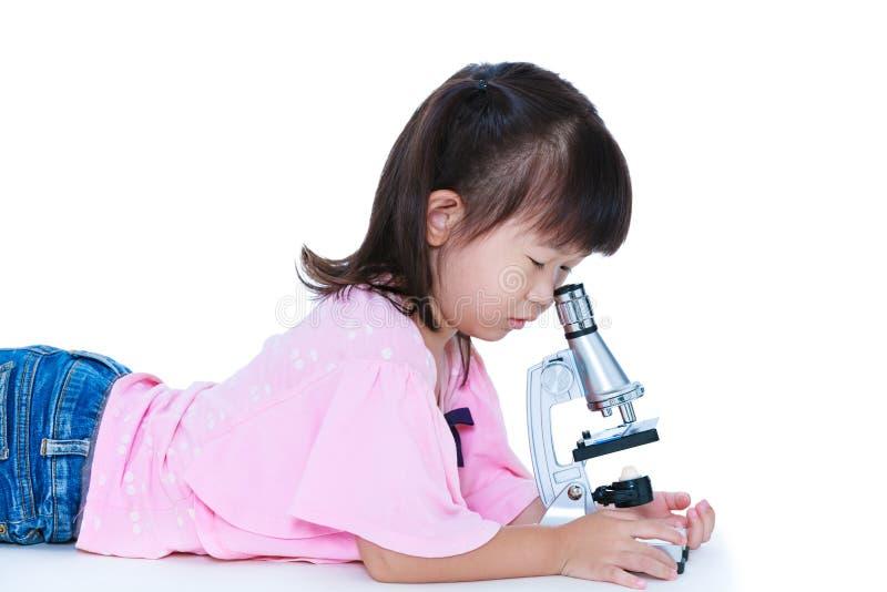 Niño asiático precioso observado a través de un microscopio Aislado en wh foto de archivo