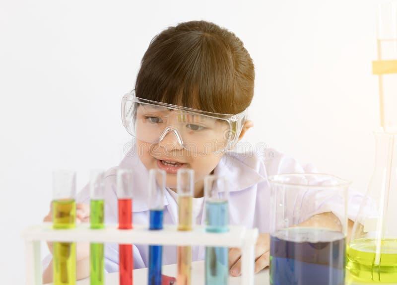 Niño asiático que juega al científico con los tubos coloridos del laboratorio imagen de archivo libre de regalías