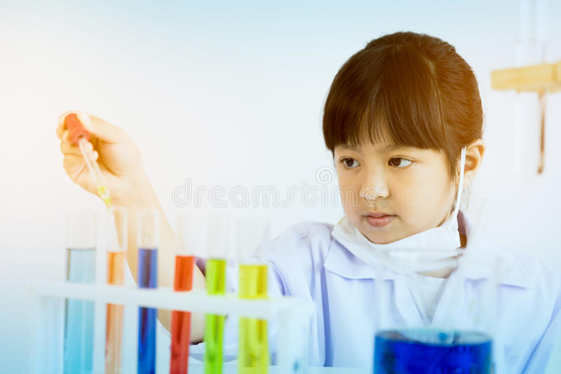 Niño asiático que juega al científico con los tubos coloridos del laboratorio imágenes de archivo libres de regalías