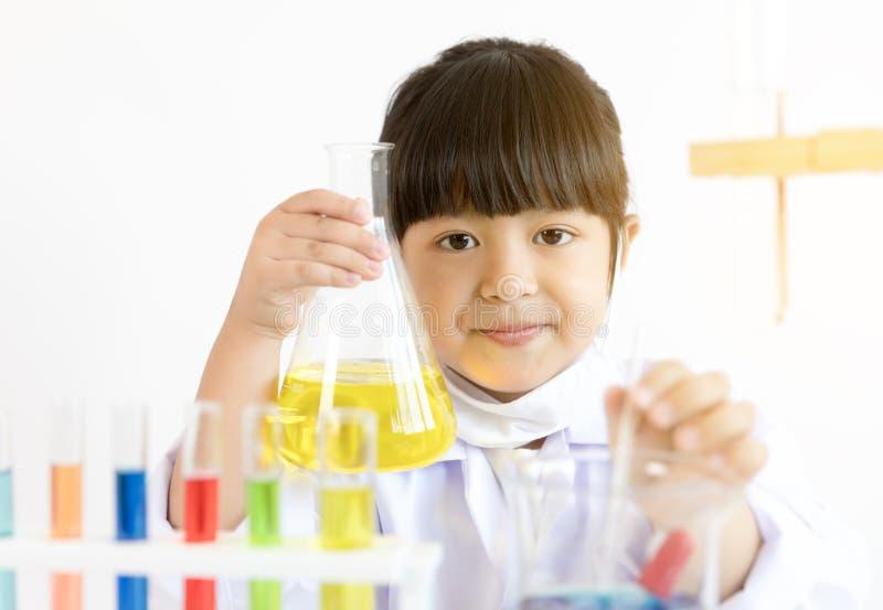 Niño asiático que juega al científico con los tubos coloridos del laboratorio foto de archivo libre de regalías