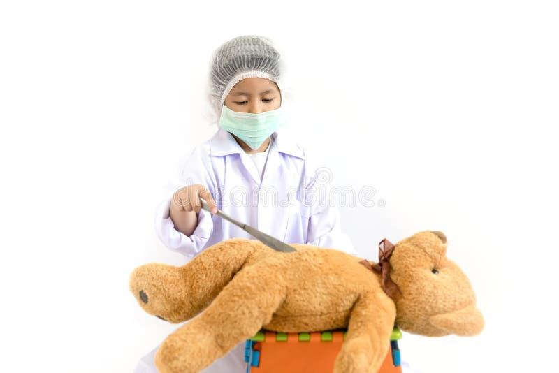 Niño asiático que juega al doctor con el oso de peluche imágenes de archivo libres de regalías