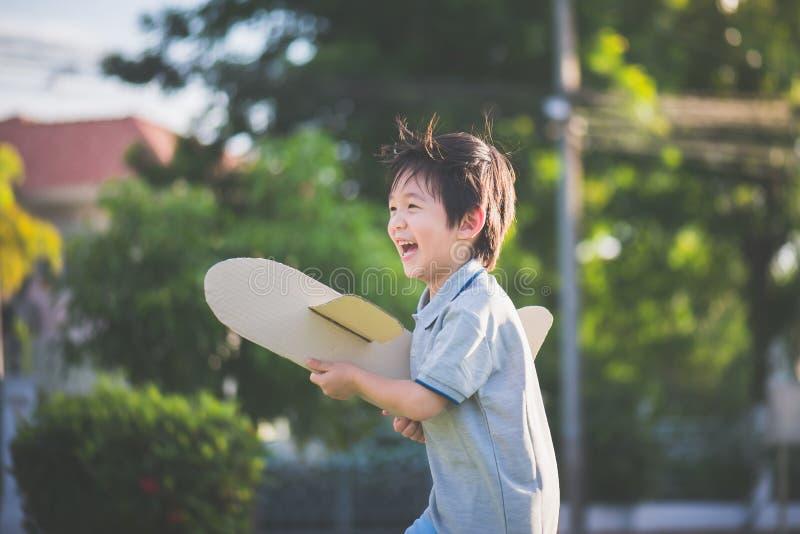 Niño asiático que juega el aeroplano de la cartulina fotografía de archivo