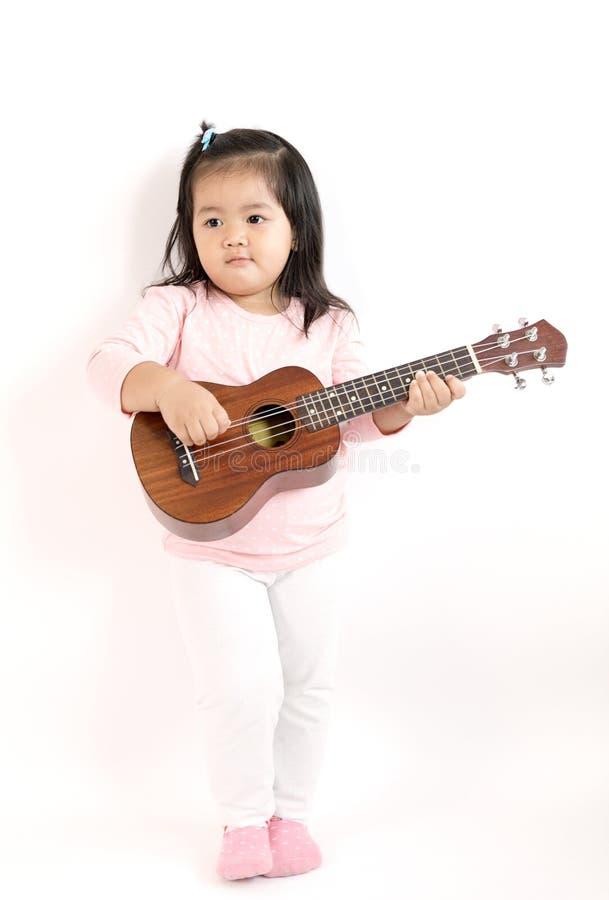 Niño asiático que juega el ukelele fotos de archivo