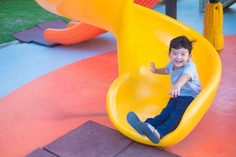Niño asiático que juega la diapositiva en el patio bajo luz del sol en verano, niño feliz en guardería o patio de escuela preesco fotografía de archivo
