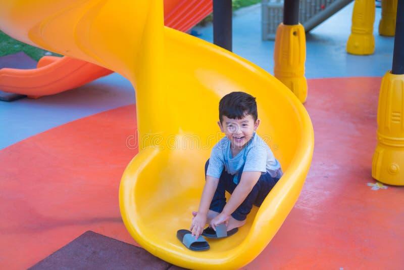 Niño asiático que juega la diapositiva en el patio bajo luz del sol en verano, niño feliz en guardería o patio de escuela preesco imagenes de archivo