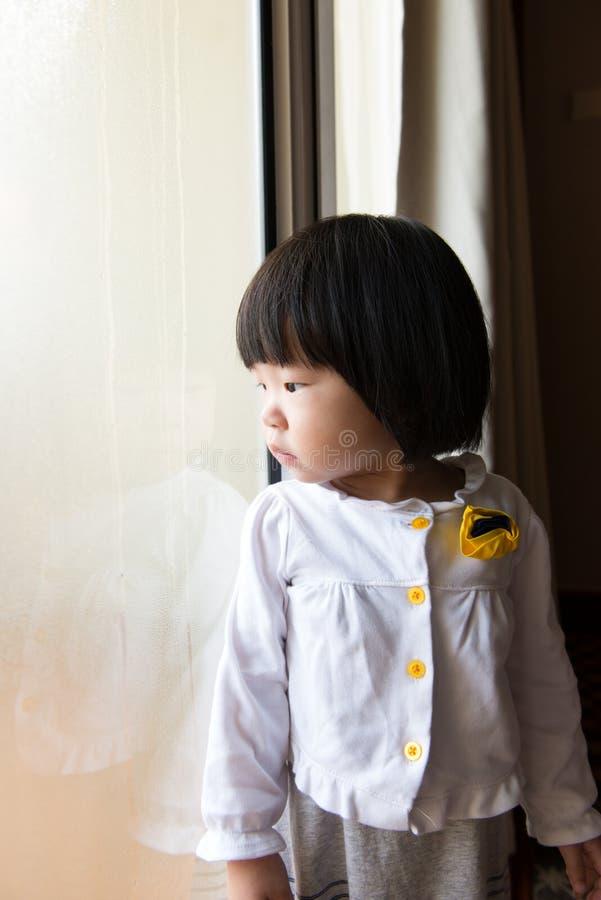 Niño asiático que mira la lluvia a través de ventana fotos de archivo