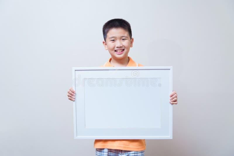 Niño asiático que muestra y que lleva a cabo el marco blanco vacío foto de archivo libre de regalías