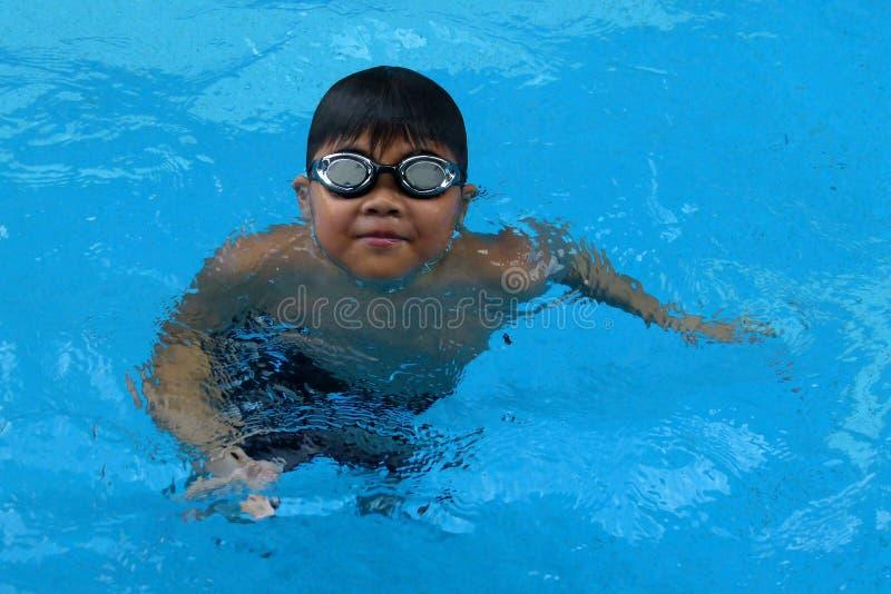 Niño asiático que se coloca en la piscina - sonrisa feliz de la cara imagenes de archivo