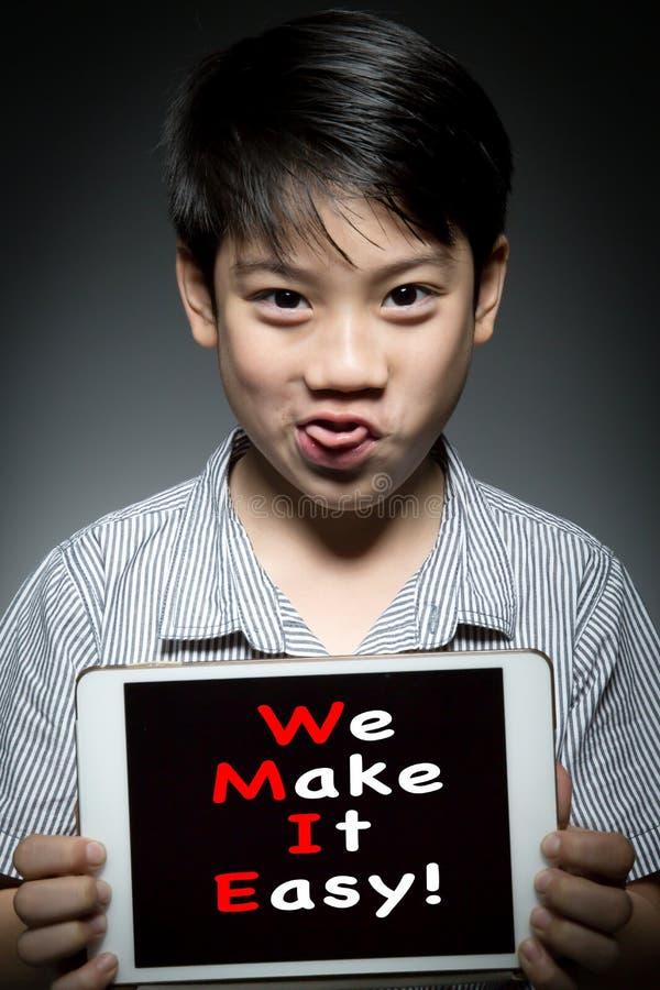 ¡Niño asiático que sostiene la tableta digital, con NOSOTROS HACEMOS LA TIC FÁCIL! fotografía de archivo