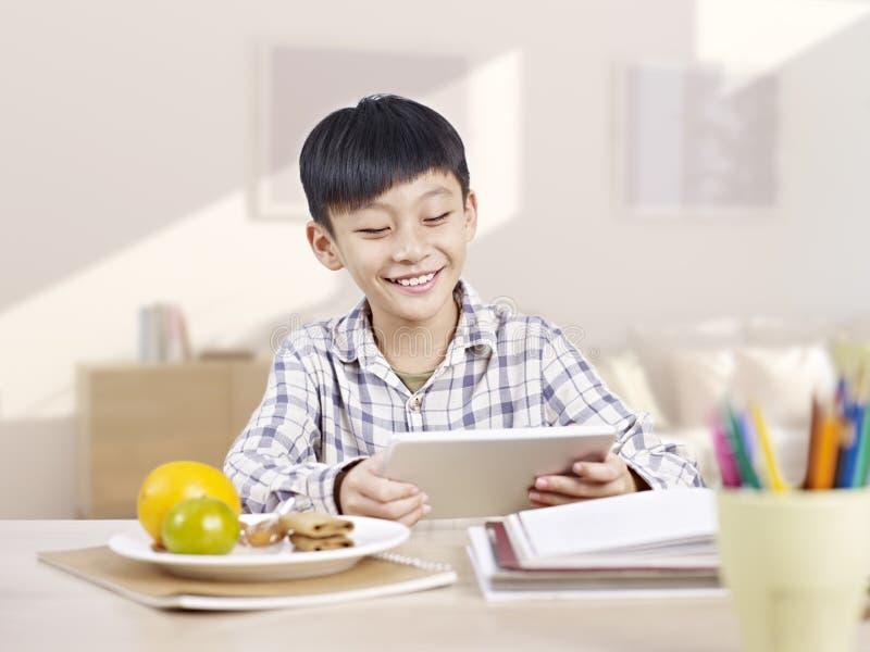 Niño asiático que usa la tableta imágenes de archivo libres de regalías