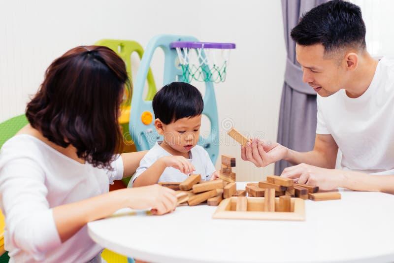 Niño asiático y padres que juegan con los bloques de madera en el cuarto en casa Una clase de juguetes educativos para el preesco imagen de archivo libre de regalías