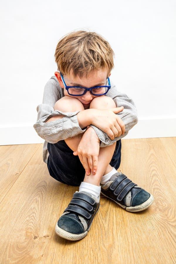 Niño asustado con las lentes y lenguaje corporal protector contra tiranizar imagen de archivo