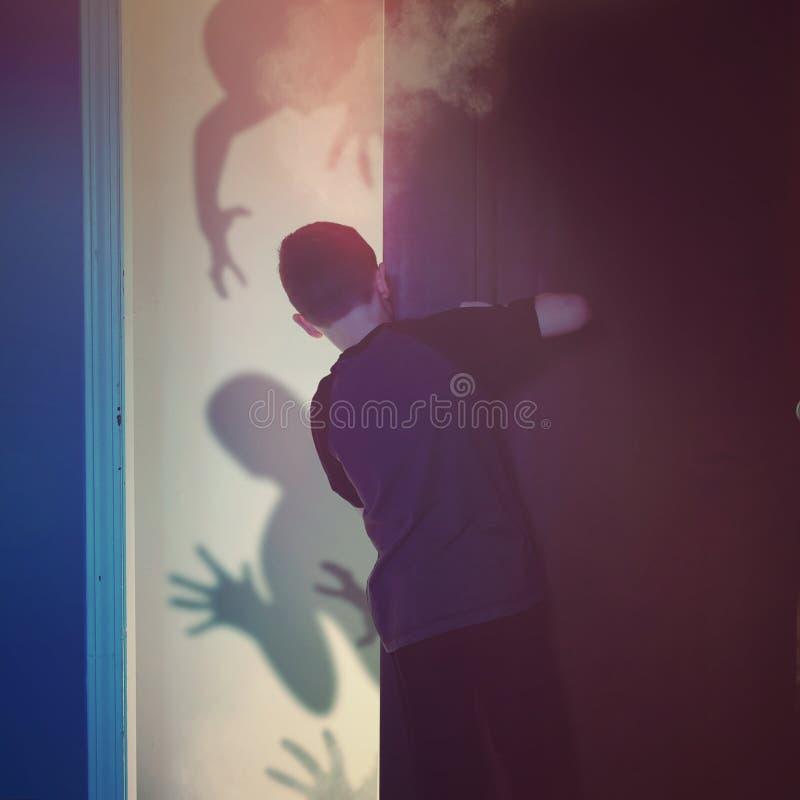 Niño asustado que mira fantasmas de la sombra foto de archivo libre de regalías