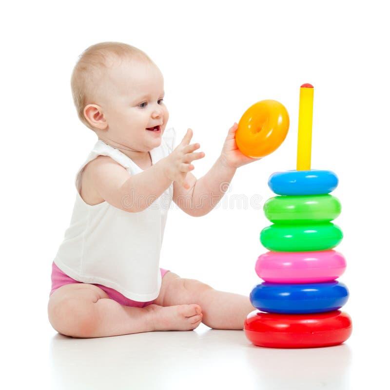 Niño bastante pequeño que juega con el juguete del color foto de archivo