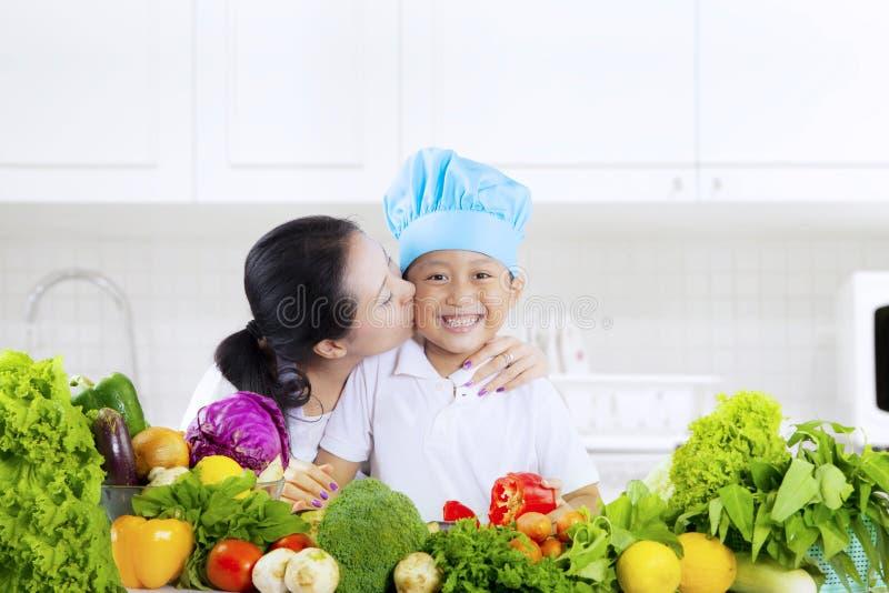 Niño besado por la madre con las verduras en cocina imagen de archivo