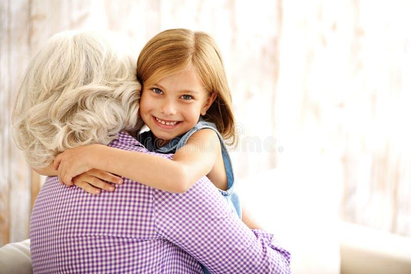 Niño bonito que abraza a su abuela imagenes de archivo