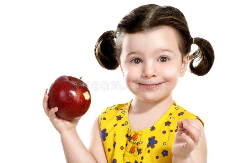 Niño bonito que sostiene una manzana roja en sus manos imagen de archivo libre de regalías