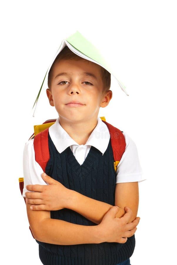 Niño cansado con el cuaderno en la cabeza fotos de archivo