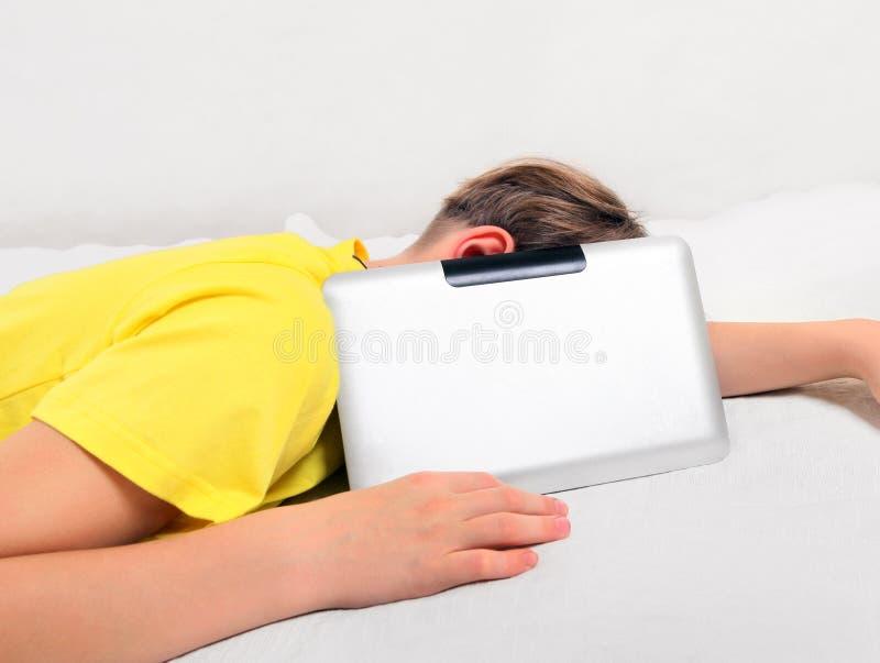 Niño cansado con la tableta foto de archivo
