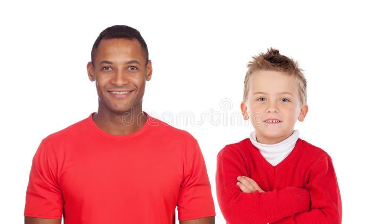 Niño caucásico con el hombre africano en cámara de mirada roja fotografía de archivo