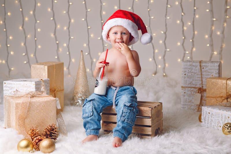 Niño caucásico en leche de consumo del sombrero de Santa Claus de la botella que celebra la Navidad o el Año Nuevo foto de archivo libre de regalías
