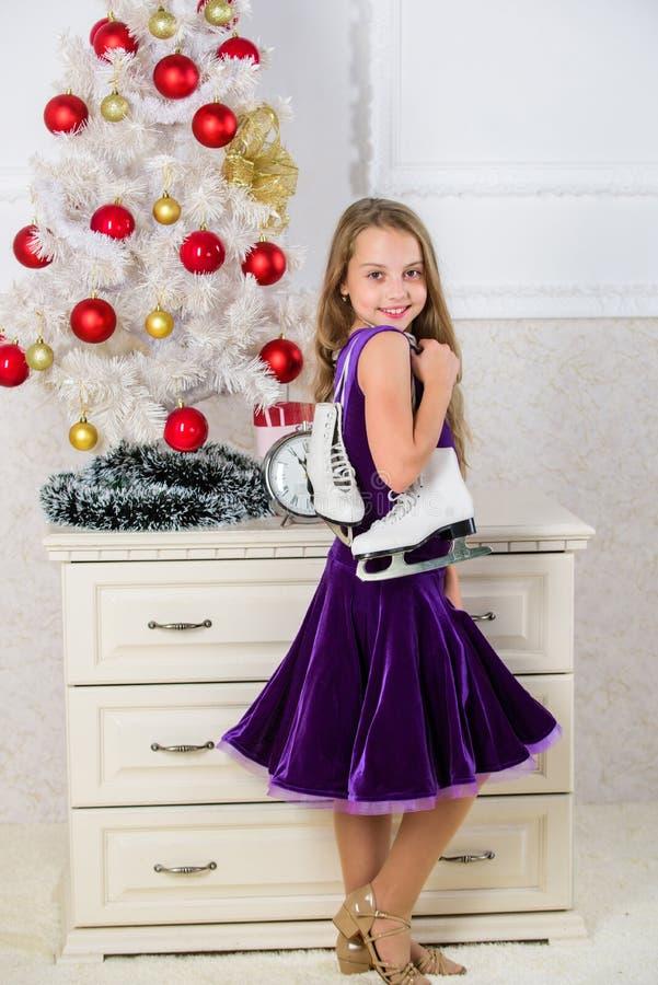 Niño cerca del regalo de los patines del control del árbol de navidad Regalo satisfecho niña de la Navidad El mejor regalo nunca  foto de archivo