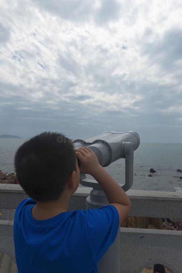 Ni?o chino usando el mar del puesto de observaci?n del telescopio fotos de archivo libres de regalías