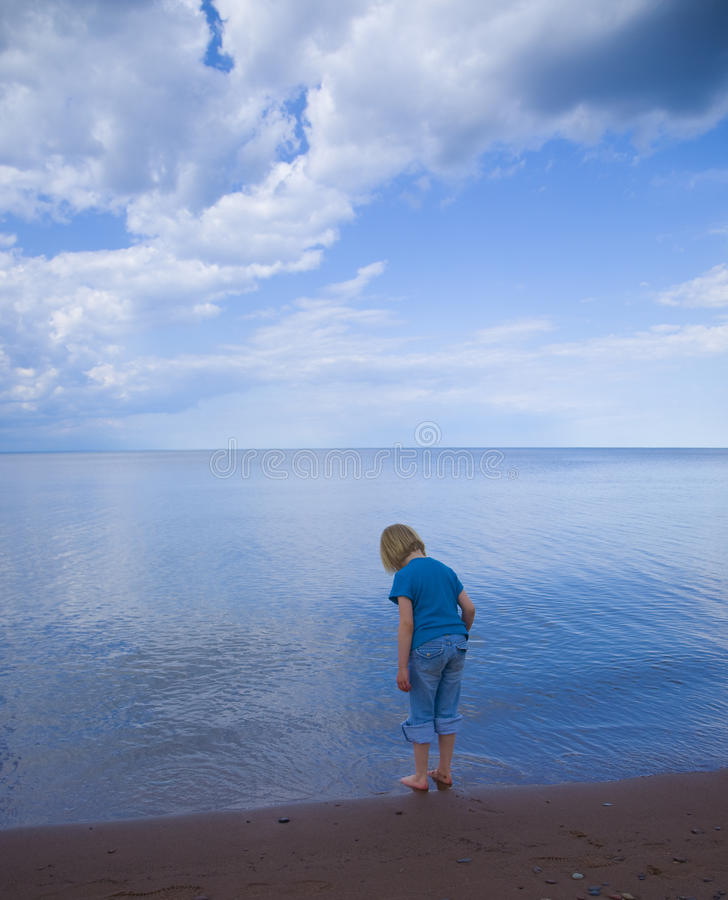 Niño, cielo, y agua azules imagen de archivo
