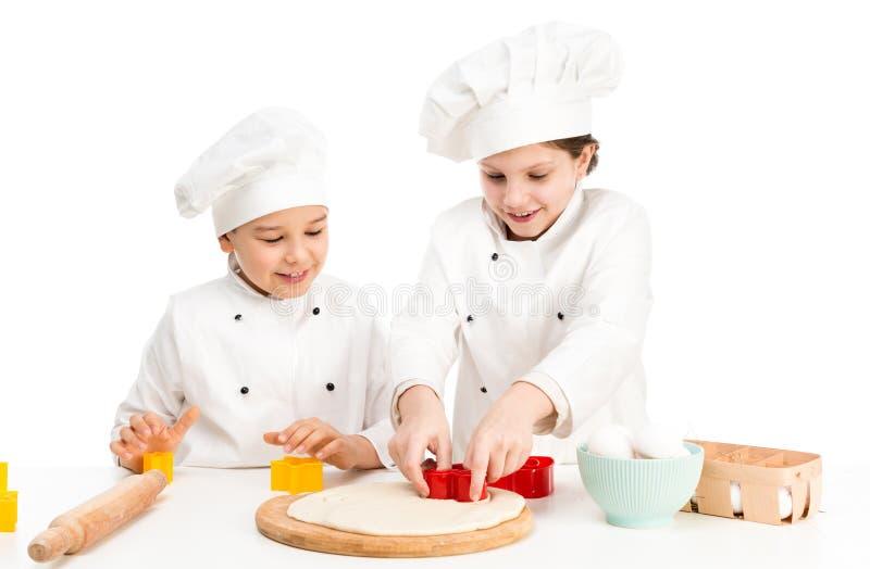 Niño-cocineros que juegan las formas para el corte del dought imagenes de archivo
