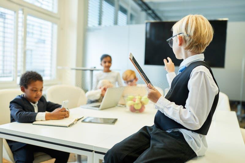 Niño como consultor de negocio o encargado con un equipo fotos de archivo libres de regalías