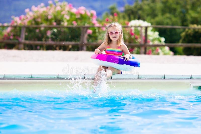 Niño con el anillo del juguete en piscina imagenes de archivo